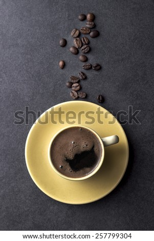 Coffee cup and coffee beans on table, from above - stock photo