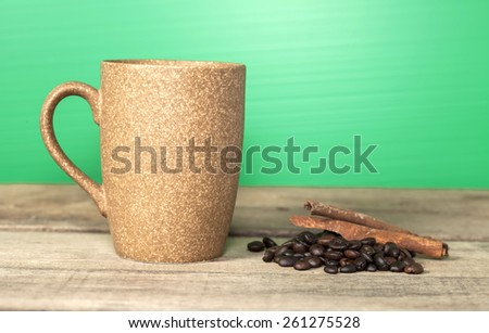 Coffee cup and coffee beans on wooden table - stock photo