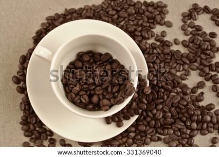 Coffee cup and coffee beans. Sepia vintage background