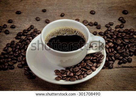 Coffee cup and coffee beans with stream on old wooden background - stock photo