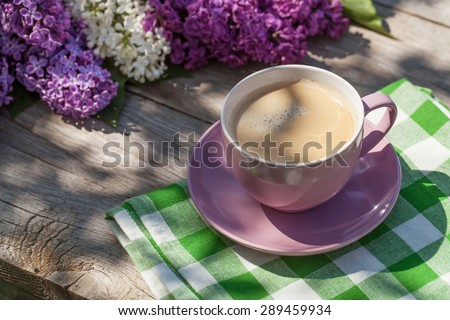 Coffee cup and colorful lilac flowers on garden table - stock photo