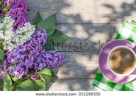 Coffee cup and colorful lilac flowers on garden table. Top view with copy space - stock photo