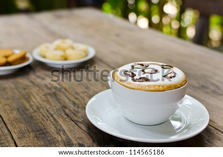 Coffee cup and cookie on the wood texture, selective focus on coffee cream.