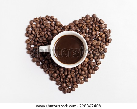 Coffee cup and heart-shaped coffee beans - stock photo