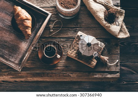 Coffee cup and ingredients on old wooden table in evening window light - stock photo