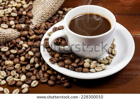 Coffee cup and jute sack full of coffee beans 6 - stock photo
