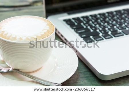 Coffee cup and laptop business on wood table