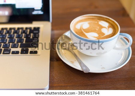 Coffee cup and laptop on table background.
