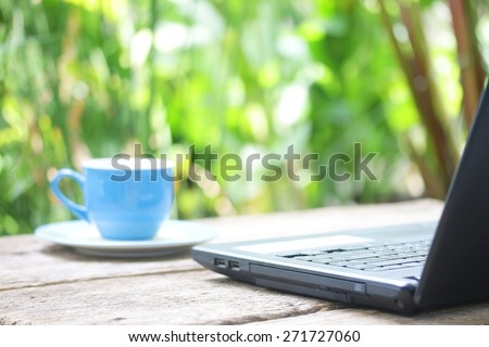 Coffee cup and laptop on wood table