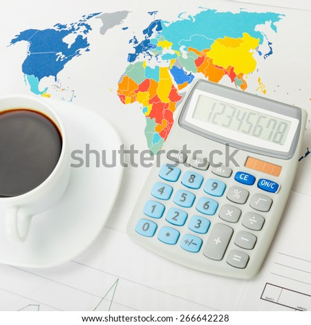 Coffee cup and neat calculator over world map - close up shot - stock photo
