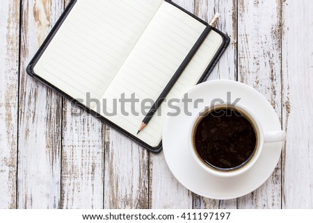 Coffee cup and notebook on white wooden table background. top view