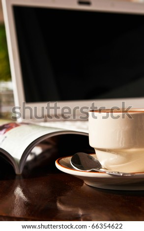 Coffee cup and notebook on wooden table - stock photo