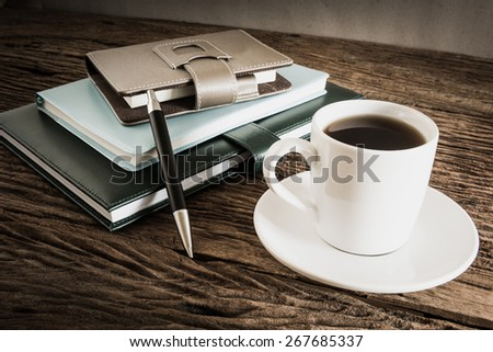 coffee cup and notebook on wooden table with against grunge wall. vintage tone