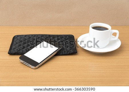 coffee cup and phone and wallet on wood table