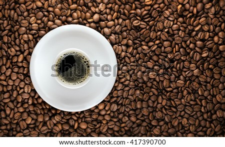Coffee cup and saucer isolated over roasted coffee beans background - stock photo