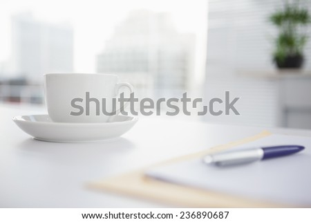 Coffee cup and saucer on desk in an office