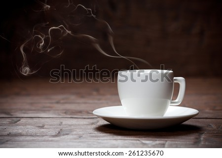 Coffee cup and saucer on old wooden table. Dark background. - stock photo