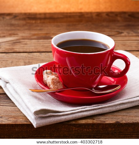 Coffee cup and saucer on tablecloth on wooden table. Dark background. Coffee concept. Selective focus. - stock photo