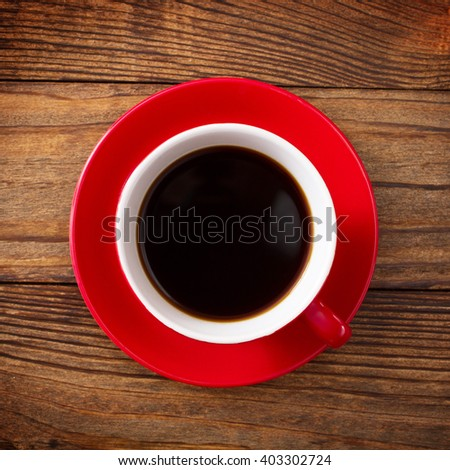 Coffee cup and saucer on wooden table top view. Dark background. Coffee concept. Selective focus. - stock photo
