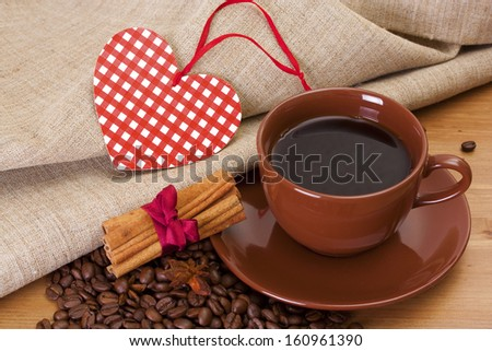 Coffee cup and saucer, paper heart, cinnamon on a wooden table