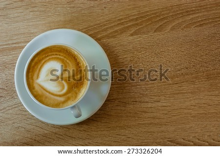 Coffee cup and saucer with heart on the wooden table - stock photo