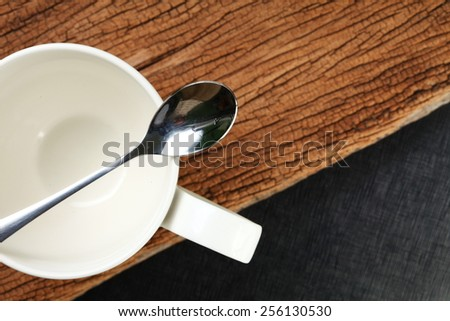 Coffee cup and shiny stainless steel spoon put on hard wood brown color and black color leather is a background represent the kitchenware concept idea.