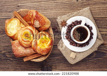 Coffee cup and sweet buns in wicker basket on old wooden table. Top view - stock photo