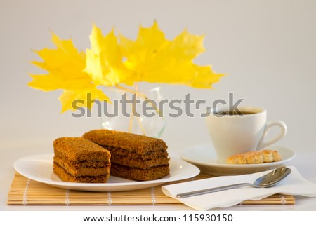 Coffee cup and sweet cake with autumn leaves on bamboo