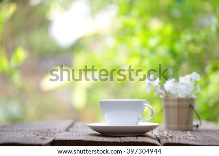 coffee cup and vintage wooden flower plot - stock photo