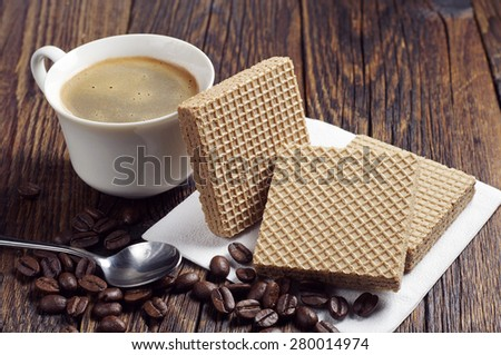 Coffee cup and wafers with caramelized condensed milk on dark wooden table - stock photo