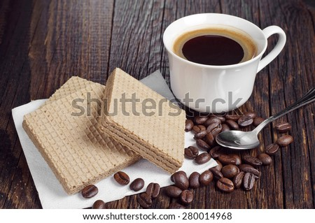 Coffee cup and wafers with chocolate on rustic wooden table  - stock photo