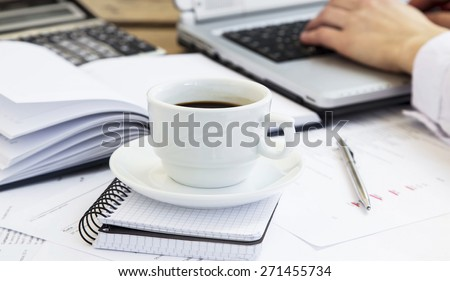 Coffee Cup at Office with Paperwork, Agenda and Businessman Working at Laptop in the Background - stock photo
