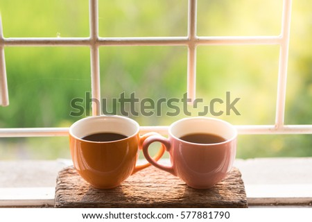 Coffee cup at window on the morning with beautiful nature and lighting background