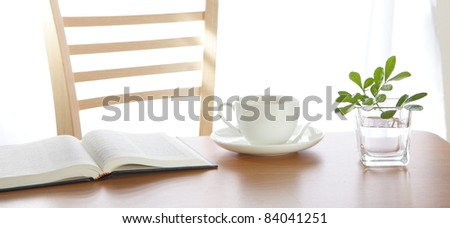 coffee Cup book and plant on wooden table - stock photo