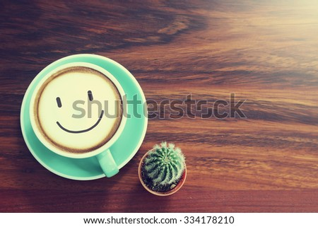 Coffee cup & Cactus on wooden background with vintage filter - stock photo