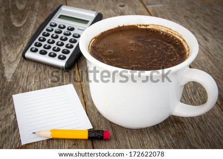 Coffee cup, calculator  and empty paper sheet with pencil on wooden background