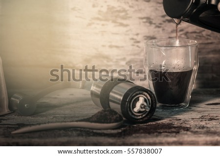 Coffee cup ,Coffee in double wall glass with hand coffee grinder coffee bag on wood table.