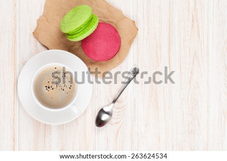 Coffee cup, colorful macarons and spoon over white wooden table with copy space - stock photo