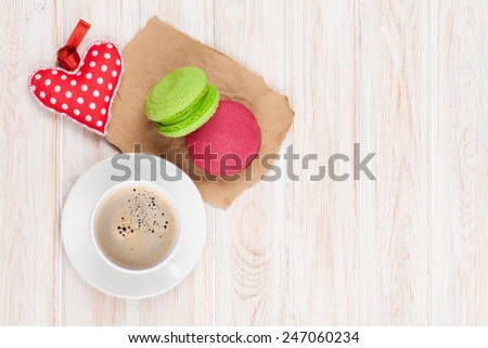 Coffee cup, colorful macarons and valentines day gift toy over white wooden table with copy space - stock photo