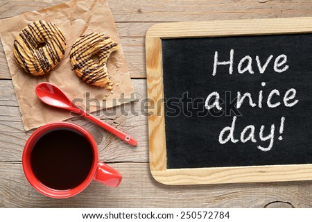 Coffee cup, cookies and chalkboard with phrase Have a nice day! - stock photo
