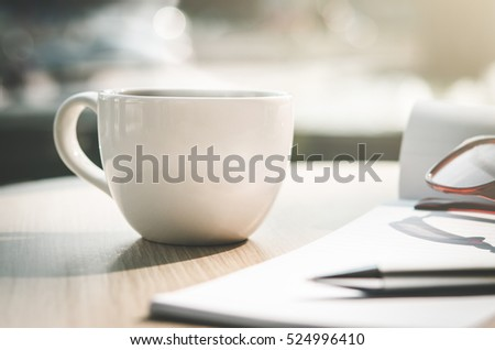 Coffee cup,eye glasses,pen and notebook on wood table in cafe(Vintage tone)