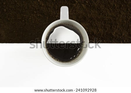 Coffee cup filled with coffee and ground coffee as background - stock photo