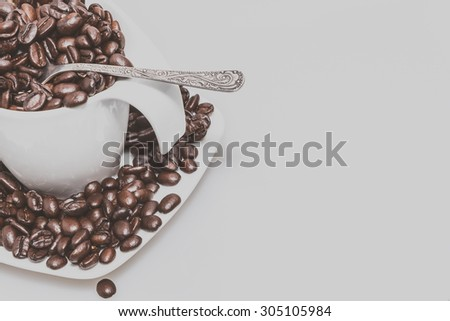 Coffee cup full of coffee beans with white background - stock photo