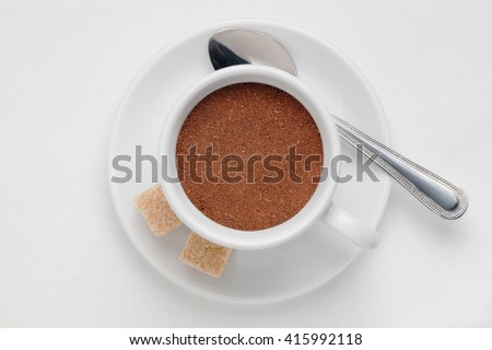 Coffee cup full of ground coffee on saucer with spoon and cane sugar cubes against white background, top view with space for text - stock photo