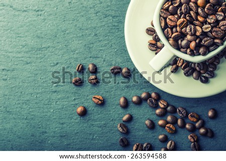 Coffee cup full of roasted coffee beans. Free space for your text - stock photo
