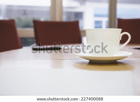 coffee cup in conference room interior with table background