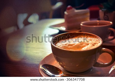 coffee cup in the coffee shop in vintage color style on mulberry texture background - stock photo