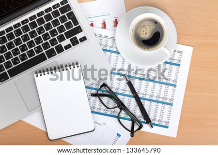Coffee cup, laptop, notepad and glasses over papers with numbers and charts. View from above - stock photo