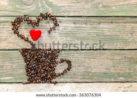Coffee cup made from beans, grain with heart on wooden background. Valentine's Day. - stock photo