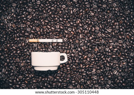 Coffee cup next to a cigarette on top of the coffee beans - stock photo